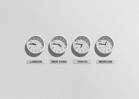 clocks on a wall giving the time of different cities